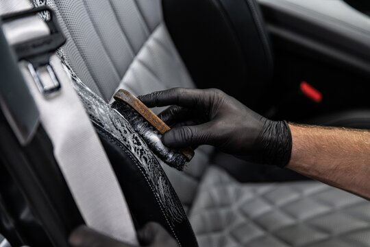 Car detailing studio worker cleaning car interior and car leather seats with a brush.