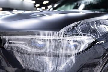Car detailing specialist installing protective transparent foil