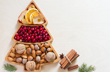 Nuts, cranberries and dried fruit in Christmas tree-shaped bowl on light background