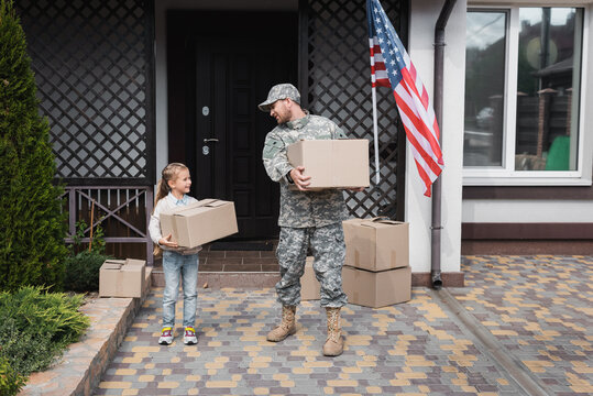 Father in military uniform and daughter holding cardboard boxes near house with American flag