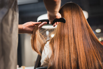 hairdresser combing hair of woman on blurred foreground