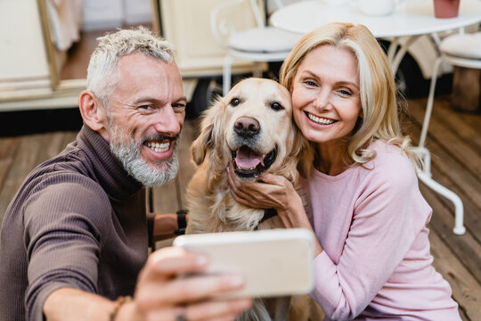 Nice-looking senior caucasian couple taking selfie with their dog on the caravan porch