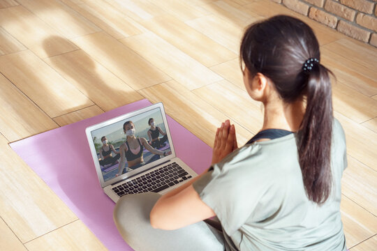 Young woman meditating watching live online tv pilates group class tutorial on laptop computer at home doing yoga virtual training fitness workout meditation exercise stream. Over shoulder screen view