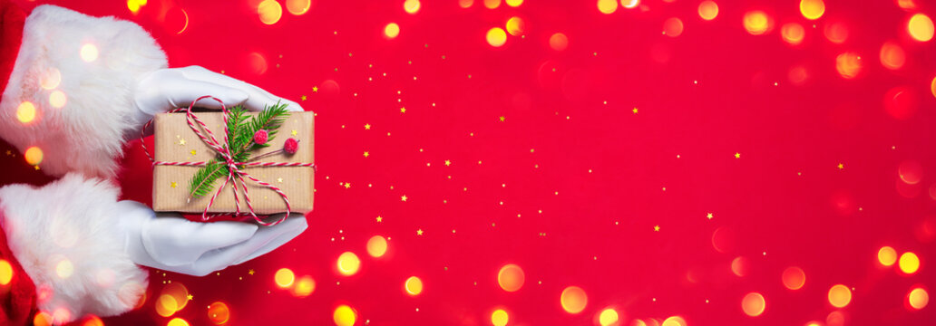 Santa Claus Give Handmade Present In Red Background - Christmas