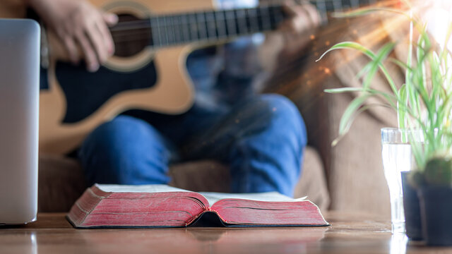 Close up christian Bible on wooden table with young male playing guitar for worship God in background, Home church during quarantine coronavirus Covid-19, Christian concept.
