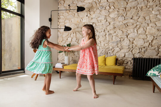 Happy young girls dancing together in living room