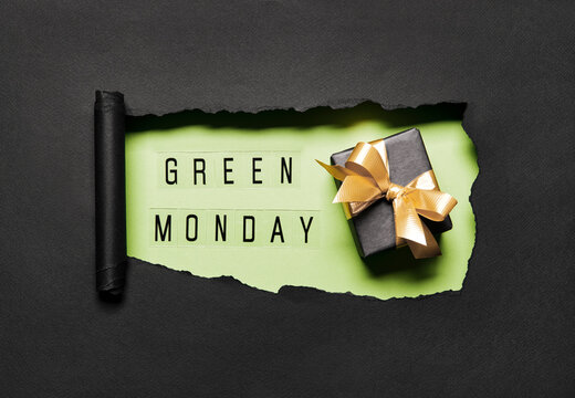 Green Monday text on green hole background with black gift box and golden bow. Shopping Discount promotion