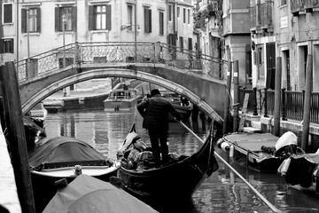 Venice, Italy, December 28, 2018 evocative black and white image of a typical Venice canal with moored boats, a connecting bridge and a moving gondola