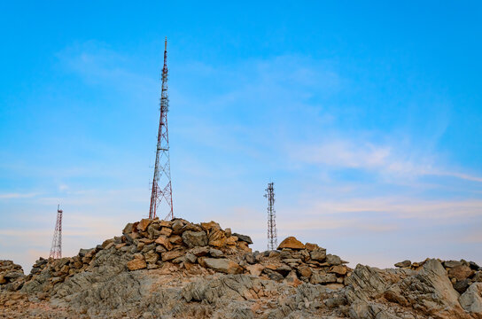 Three mobile towers on rocky mountains jutting out to the blue sky. From Muscat, Oman.
