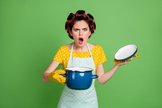 Photo of amazed crazy girl open cover saucepan discover someone eat all soup scream wear yellow pot holder dotted t-shirt hair rollers isolated over green color background