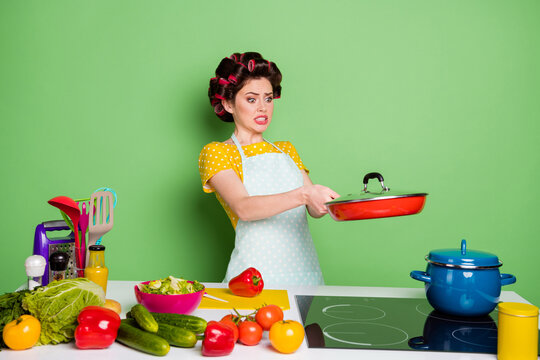 Portrait of her she nice attractive lovely pretty worried nervous housewife cooking domestic dish holding hot meal mushroom oops problem isolated over green pastel color background