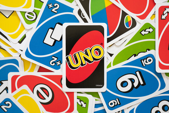 Uno game cards scattered all over the frame and one card showing the reverse side with Uno logo close-up