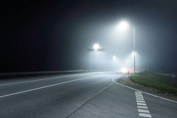 Panoramic view of the illuminated new highway in a fog at night, street lights close-up. Moonlight. Dark urban scene. Europe. Transportation, logistics, travel, tourism, road trip, freedom, driving Fotomurales