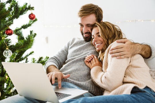 Beautiful happy couple hugging and using laptop while resting
