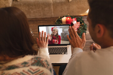Rear view of couple waving while having a videocall with woman in santa hat waving while holding gif