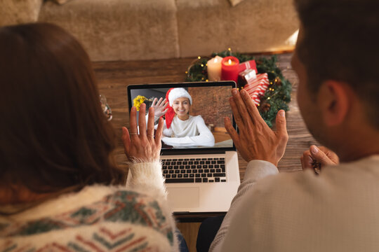 Rear view of couple waving while having a videocall with woman in santa hat waving on laptop at home