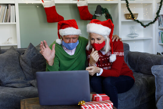 Senior couple in santa hat wearing face mask waving while having a video call on laptop at home