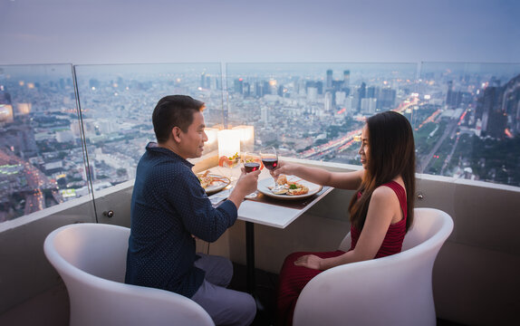 Young beautiful couple having romantic dinner on rooftop at night.
