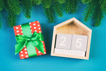 Wall Mural - Top view of fir tree, wooden calendar and gift box on colorful background. The twenty fifth of December. Merry Christmas time with empty space for your design