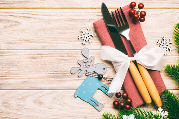 Wall Mural - Top view of holiday objects on wooden background. Utensils tied up with ribbon on napkin. Christmas decorations and reindeer with copy space. New year dinner concept