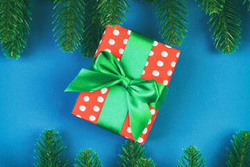 Wall Mural - Top view of colorful holiday background made of fir tree and gift box. Happy New Year concept with copy space