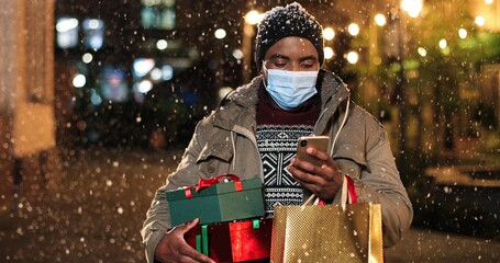 Portrait of man standing and texting on mobile phone. Young African American happy male with little Christmas tree and shopping bags typing on smartphone while snowing. Winter holidays concept Fotomurales