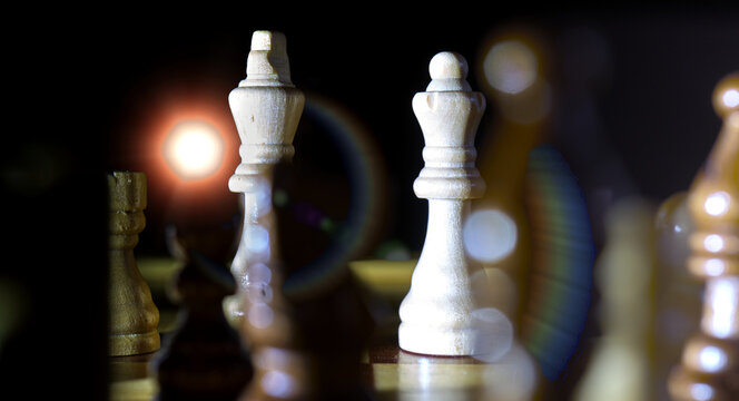 Hard from behind illuminated chessboard with the queen and the king in focus, light source and flare visible, sharp shadows and lights