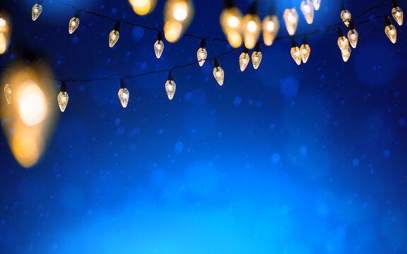 Christmas lights over Snowy dark blue sky background