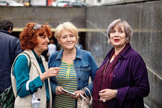 Senior cheerful caucasian women stand near underpass.