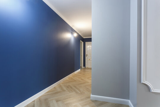 Empty unfurnished corridor with minimal preparatory repairs with crown moulding. interior of white and blue walls