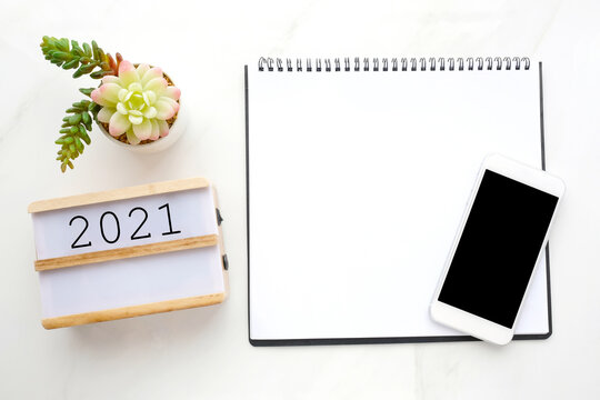 2021 on wood box and blank notebook paper, mobile phone with blank screen on white marble background, 2021 new year mock up, template, flat lay