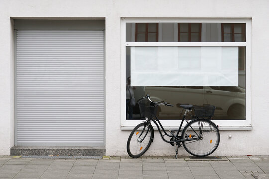 blank vacancy sign or poster with copy space in empty store window with bicycle parked outside closed shop