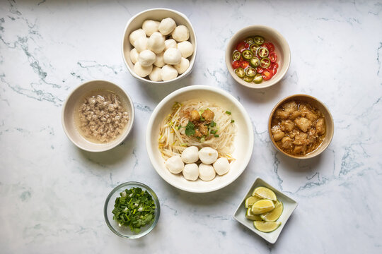 Rice stick noodles with fish ball in white bowl. Garlic cracklings with lard, mined pork, pickled chili, lime and coriander with spring onion various ingredients and condiment on table.
