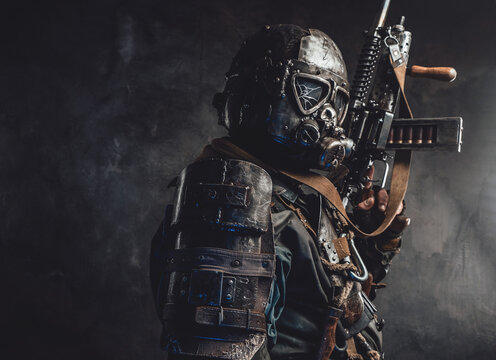 Ragged apocalyptic survivor in gas mask and custom armour poses in dark background holding his gun.