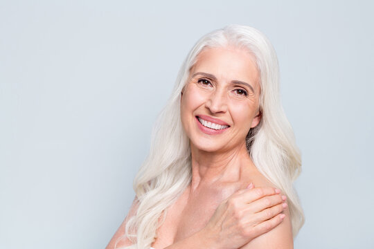 Close-up portrait of her she nice attractive cheerful grey-haired elderly lady washing smoothing skin peeling isolated on gray pastel color background