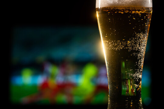 Close-up of fresh foaming light beer in a glass and football on TV on background. Sports bar concept