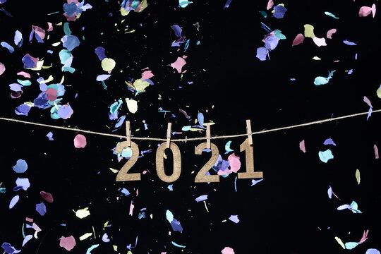 Año nuevo de 2021 en números de madera dorada colgados de una cuerda con pinzas de oficina sobre fondo negro y confeti cayendo