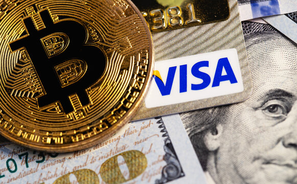 bitcoin cryptocurrency with Visa credit card and dollars, money. Visa - American multinational company providing services of payment operations. Moscow, Russia - August 16, 2020