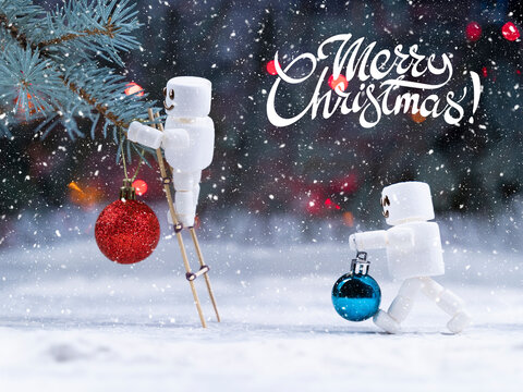 Jolly cute marshmallow snowman decorate christmas tree by  red and blue christmas tree balls on snowing forest background merry christmas lettering