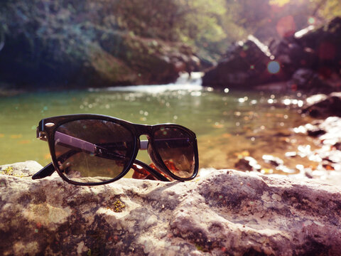 waterfall in the mountains, rocks close sunglasses on rocks