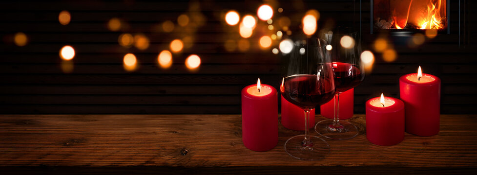 Glasses of red wine with candles on rustic wood in front of a log fire and golden bokeh lights. Horizontal background for celebrations and cozy evenings with space for your text and decorations.