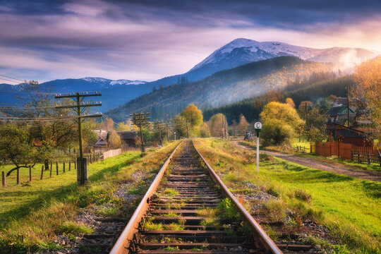 Railroad in mountains with snowy peaks at sunset in autumn. Industrial landscape with railway station, orange trees, green grass, buildings, rocks, purple sky with clouds in fall. Railway platform