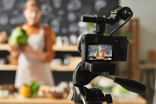 Young woman holding vegetable and recording the video about food for her blog