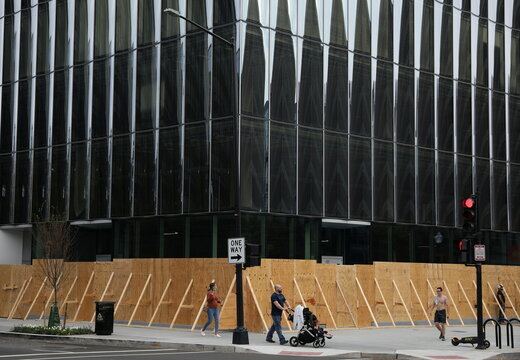 Pedestrians walk past an office building surrounded by plywood ahead of potential presidential election protests in Washington