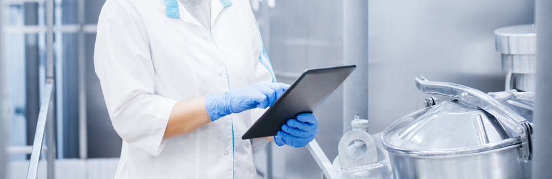 Factory worker inspecting production line tanker in of dairy factory with computer tablet. Concept food industry banner