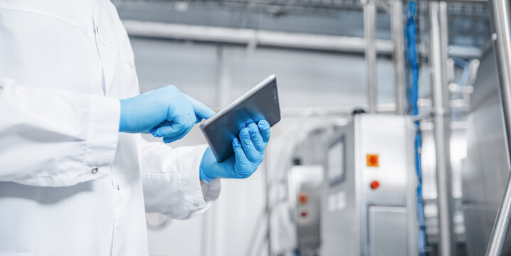 Man worker holding tablet computer checking production line dairy factory food industry. Copy space banner