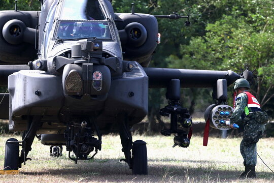 A soldier loads training rockets into a pod on an AH-64E Apache attack helicopter during 'Combat Readiness Week' drills in Hsinchu, Taiwan