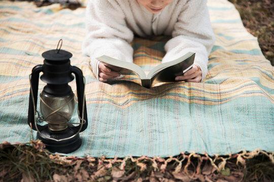 森の中でレジャーシートに寝転びながら本を読む女性