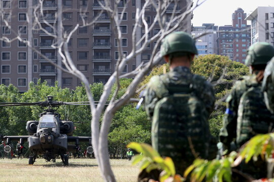 Soldiers observe an AH-64E Apache attack helicopter during 'Combat Readiness Week' drills in Hsinchu,