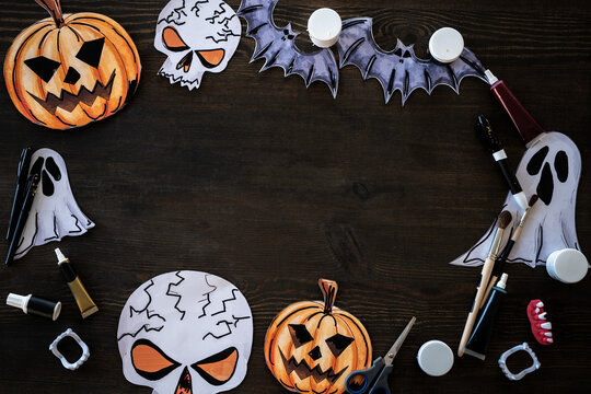 Halloween frame made of pumpkin, rat, ghost and skeleton paper pictures placed with art supplies on wooden table